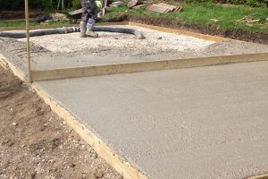 Concrete layer of base being pumped in and tampered level